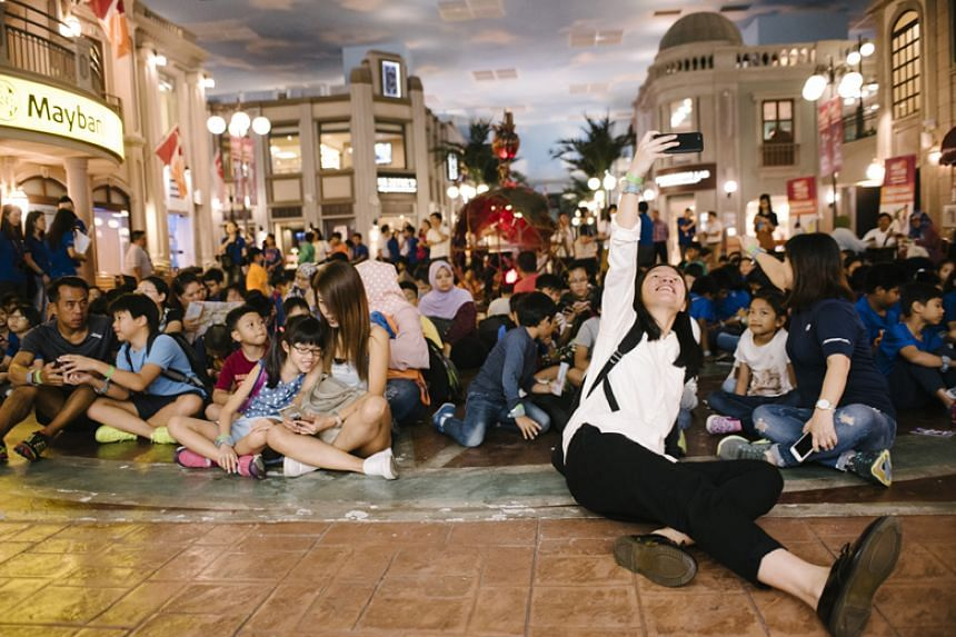 A caregiver takes a wefie with children at KidZania Singapore at the launch of Sentosa Gives 2018, the seventh edition of Sentosa Development Corporation's signature community outreach programme.