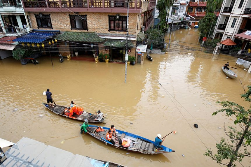 People travel by boat past buildings flooded by Typhoon Damrey in Vietnam's ancient Unesco heritage town of Hoi An on Nov 7, 2017.