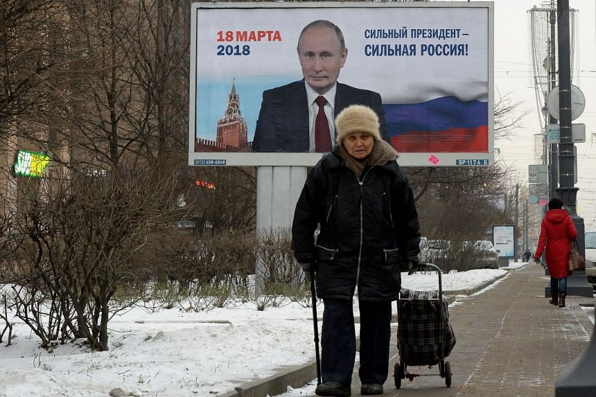 A woman passes by a billboard with an image of Russia's President Vladimir Putin in Saint Petersburg, on Jan 12, 2018.