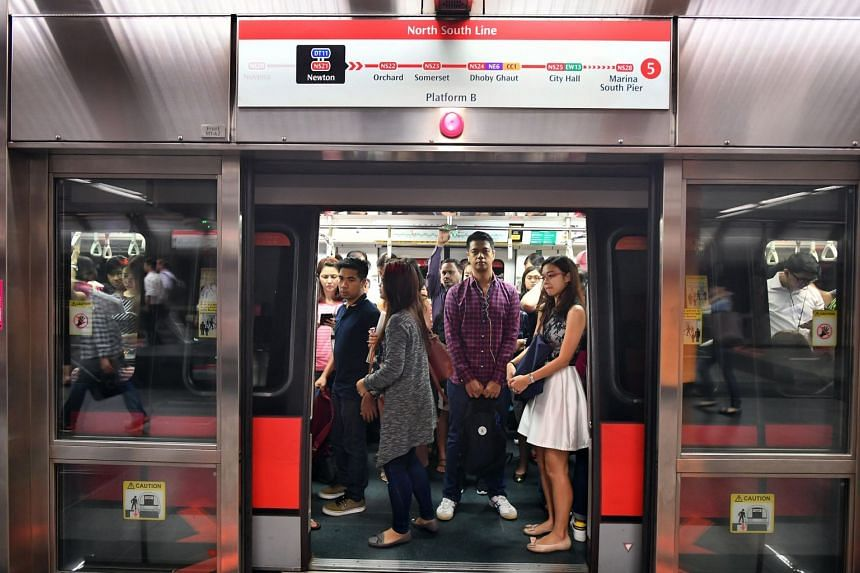 Commuters on a crowded train travelling from Newton to Marina South Pier MRT station.