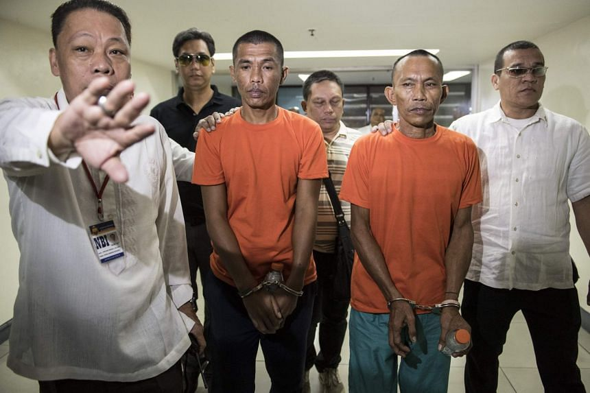 Suspected militants Hood Abdullah (in front, second from left) and Jimmy Bla are escorted by National Bureau of Investigation agents to a press conference at the bureau's headquarters in Manila, on March 12, 2018.