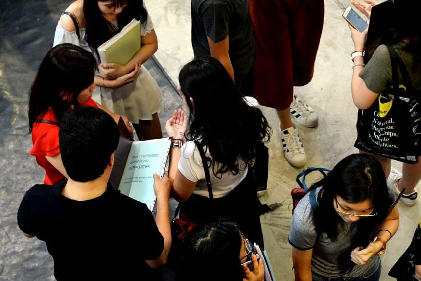 Students checking their A-level result slips in Nanyang Junior College, one of the four schools affected by the theft of exam scripts for Chemistry Paper 3, on Feb 23, 2018.