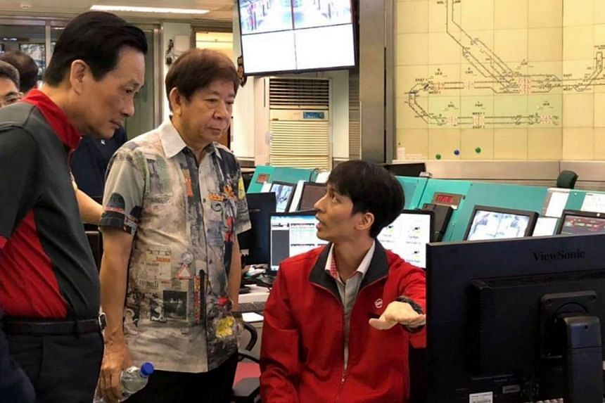 Train service controller Tan Ming Hui (right) speaking to Transport Minister Khaw Boon Wan on a recent visit to SMRT's Operation Centre, where he observed testing of the new signalling system. With them is SMRT chairman Seah Moon Ming.