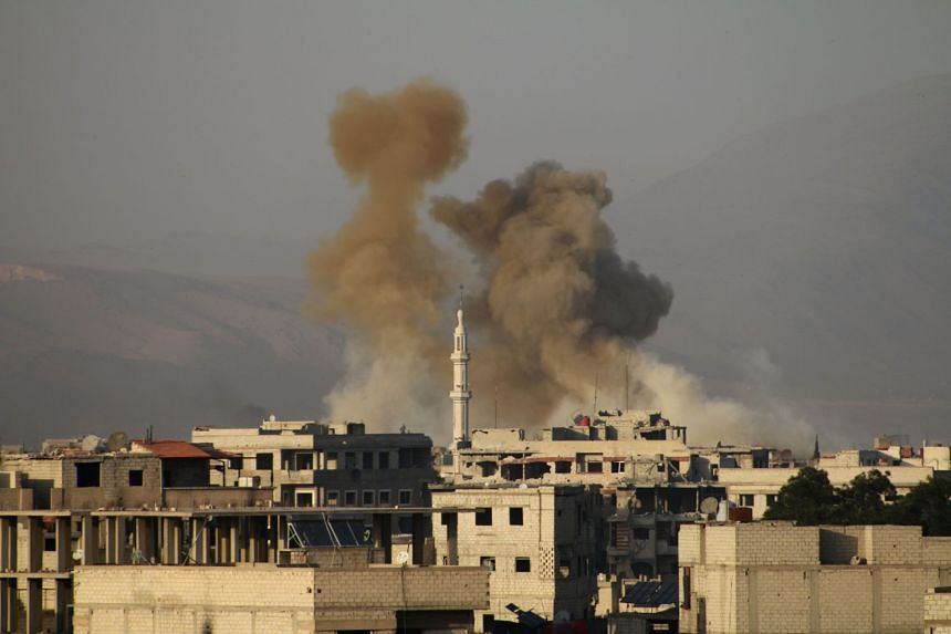 Smoke billows following Syrian government bombardment on the rebel-controlled area of Saqba, in the besieged Eastern Ghouta region on the outskirts of the capital Damascus, on March 11, 2018.