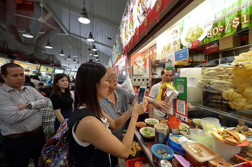 Customer Neo Ann Chee, 36, paying for her lunch at the Tanjong Pagar Plaza Market and Food Centre using the QR code payment system offered at the stall. Of the 50 stalls there, 45 display the Nets QR code and have Nets' card readers to let consumers