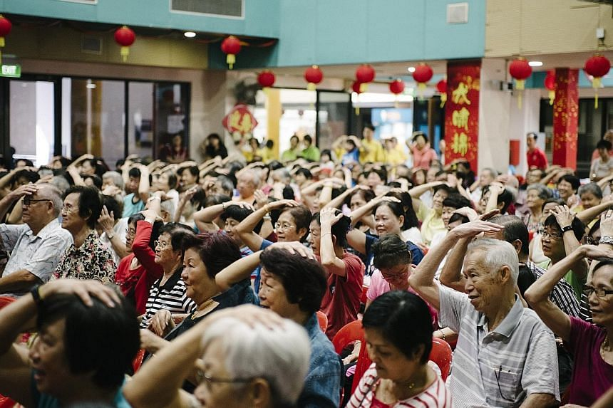 The crowd at the Bukit Panjang Community Club on Sunday engaging in a mass demonstration of dual-task activities - which have been shown to help improve memory - under the Healthy Ageing Promotion Programme For You.