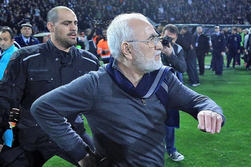 Ivan Savvides, Russian-born Greek businessman and owner of Paok Salonika, carrying what appeared to be a gun in a holster. He entered the pitch accompanied by bodyguards after the referee disallowed a goal by his side against AEK Athens, whose player