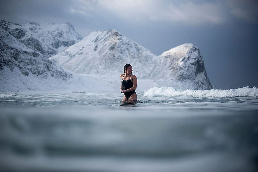 A young woman taking a quick dip in Unstad in northern Norway's Lofoten islands, within the Arctic Circle, on Sunday. The air temperature was a chilly -5 deg C, while the water temperature was 4 deg C.
