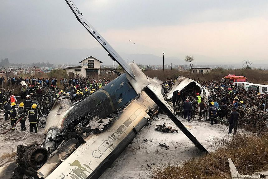 Rescue workers at the scene of the plane wreckage at the Kathmandu airport yesterday. The aircraft, operated by US-Bangla Airlines, was on a flight from Dhaka when it hit an airport fence and burst into flames, according to the airport. It had 71 peo