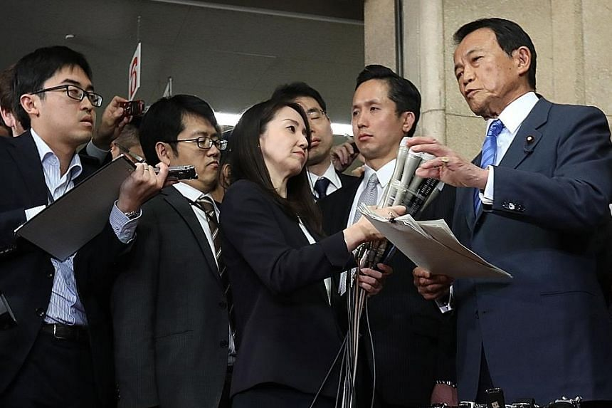 Finance Minister Taro Aso (in blue) yesterday apologised for his ministry's actions, but said he did not intend to step down. He said several officials at his ministry's division in charge of the land sale were involved in altering the documents to m