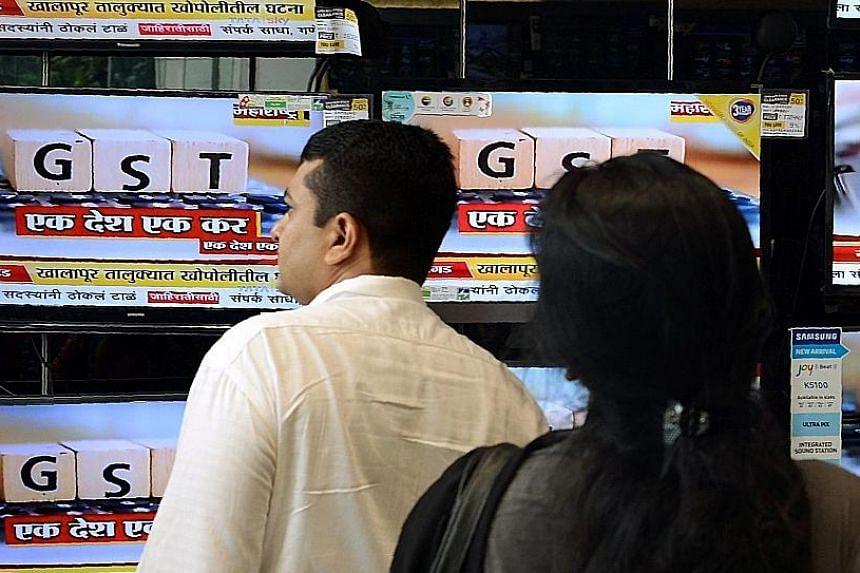 News on the new GST regime being reported on TV in Mumbai last June. Even though the GST has simplified a complex system of multiple federal and state taxes, eight months into its launch, it is still plagued by issues like online portal glitches and