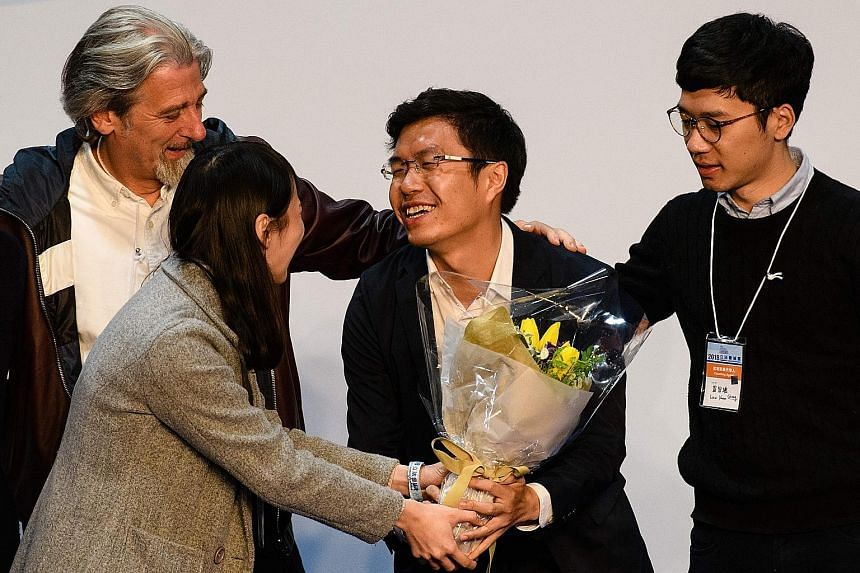 Pro-democracy candidate Au Nok Hin is congratulated by (from left) activist Paul Zimmerman and Demosisto members Agnes Chow and Nathan Law after his by-election win yesterday.