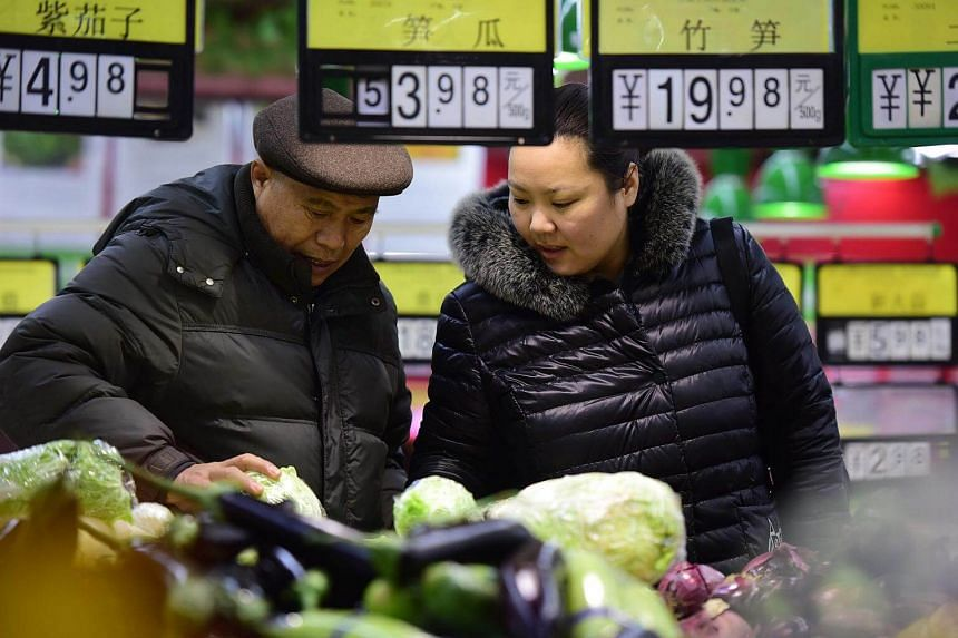 People selecting vegetables at a supermarket in Fuyang, in eastern China's Anhui province, on Feb 9, 2018.