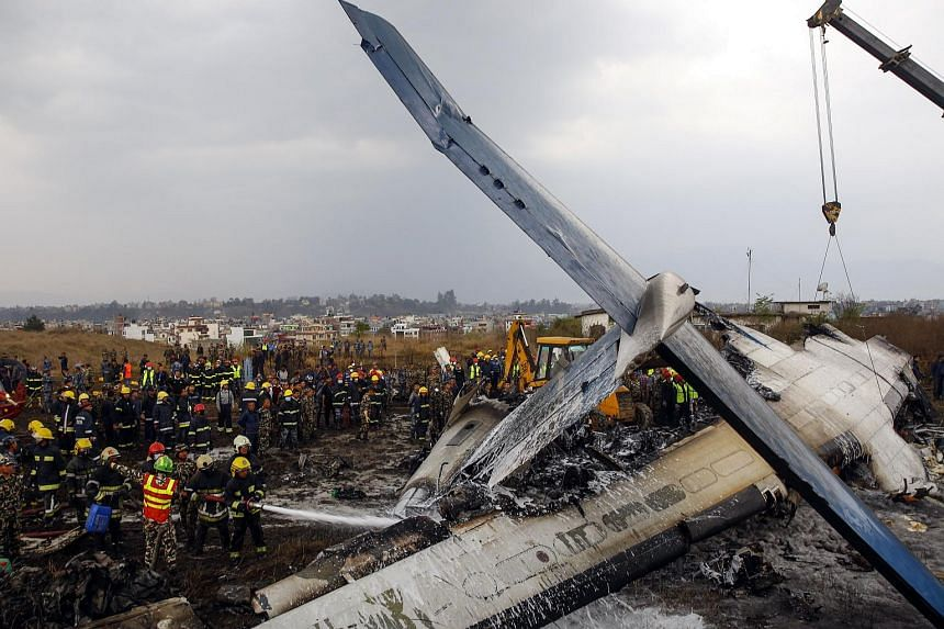 Rescue teams next to a wreckage of a plane that crashed at the main airport Tribhuvan International Airport in Kathmandu, Nepal, on March 12, 2018.