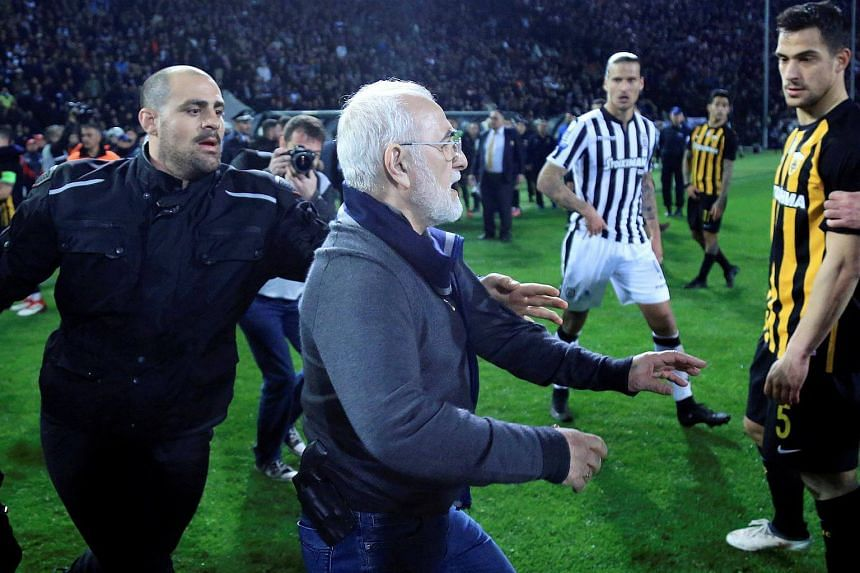 Owner of PAOK Salonika, Ivan Savvides (centre), with a gun in a holster, enters the pitch after the referee annulled a goal of PAOK during their soccer match against AEK Athens in Toumba Stadium in Thessaloniki, Greece, on March 11, 2018.