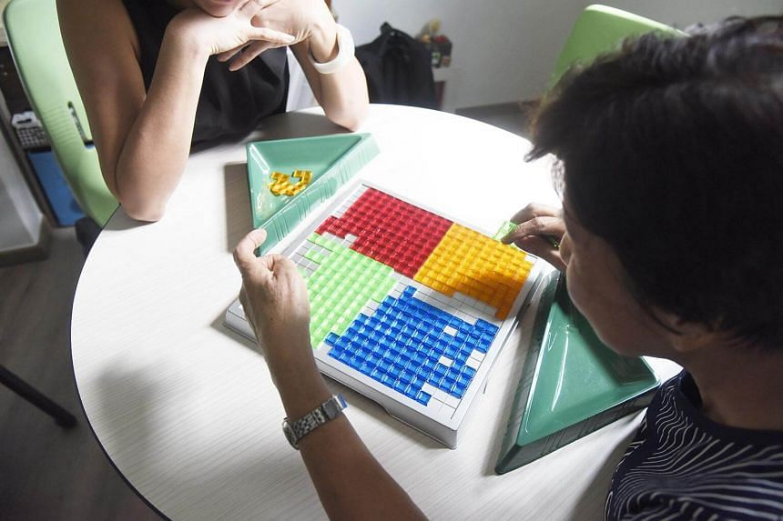 A woman with dementia performing a cognitive activity at The Care Library facilitated by a centre employee.