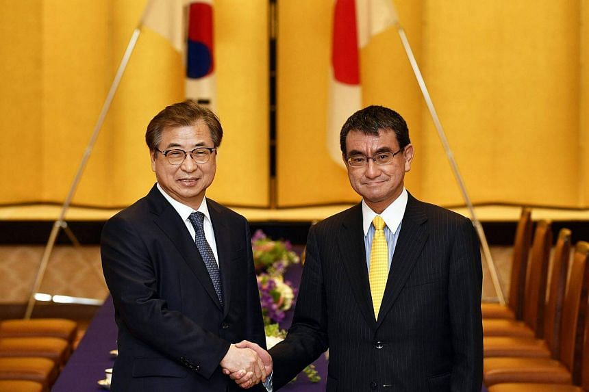 South Korea's National Intelligence Service chief Suh Hoon (left) shakes hands with Japan's Foreign Minister Taro Kono before their meeting at the Iikura Guest House in Tokyo, on March 12, 2018.