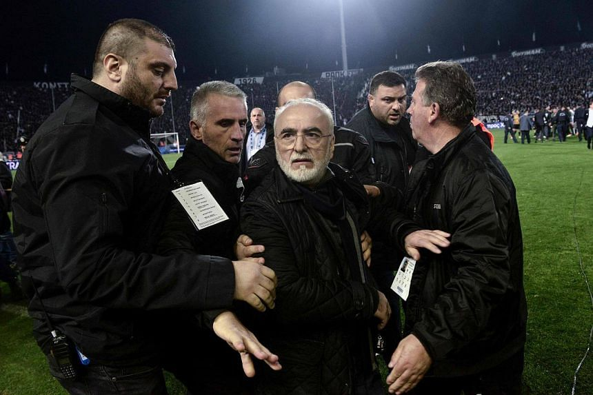 PAOK president Ivan Savvidis (centre) is escorted out of the pitch during the Greek Superleague football match between PAOK Thessaloniki and AEK Athens in Thessaloniki, on March 11, 2018.