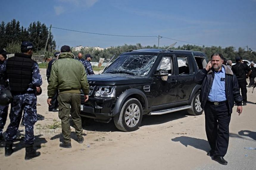 Hamas security officials inspect one of the cars of Palestinian Prime Minister Ramil Hamdallah's convoy that was targeted in an attack after his arrival in Beit Hanun town.