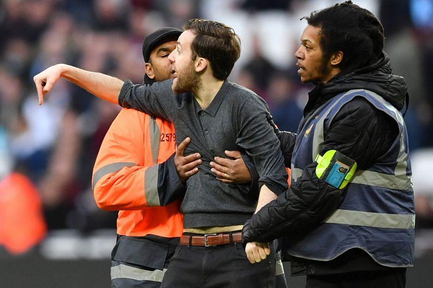 A pitch invader is handled by security during the English Premier League football match between West Ham and Burnley at The London Stadium, in east London on March 10, 2018.
