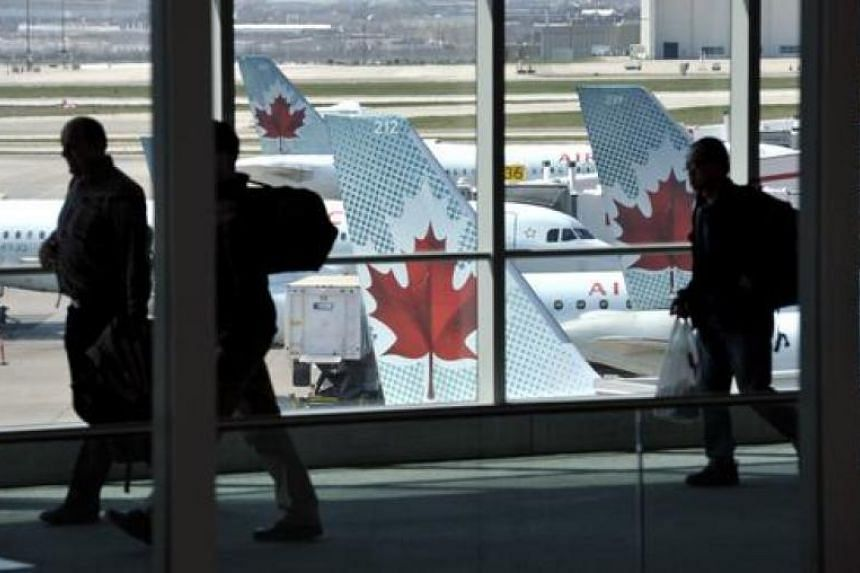 Passengers walk past Air Canada planes on the runway at Pearson International Airport in Toronto in this April 13, 2012, file photo.