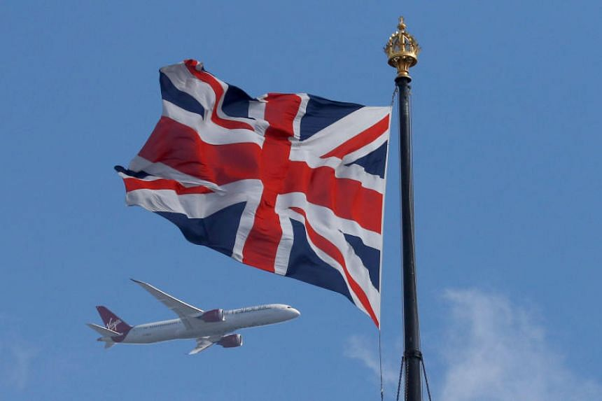 A Virgin Atlantic passenger jet flies past the Union Flag above the Houses of Parliament in Westminster, in central London, Britain on June 24, 2016.