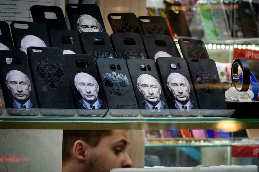 A kiosk vendor sells phone covers featuring Russian President Vladimir Putin in Moscow on March 13, 2018.
