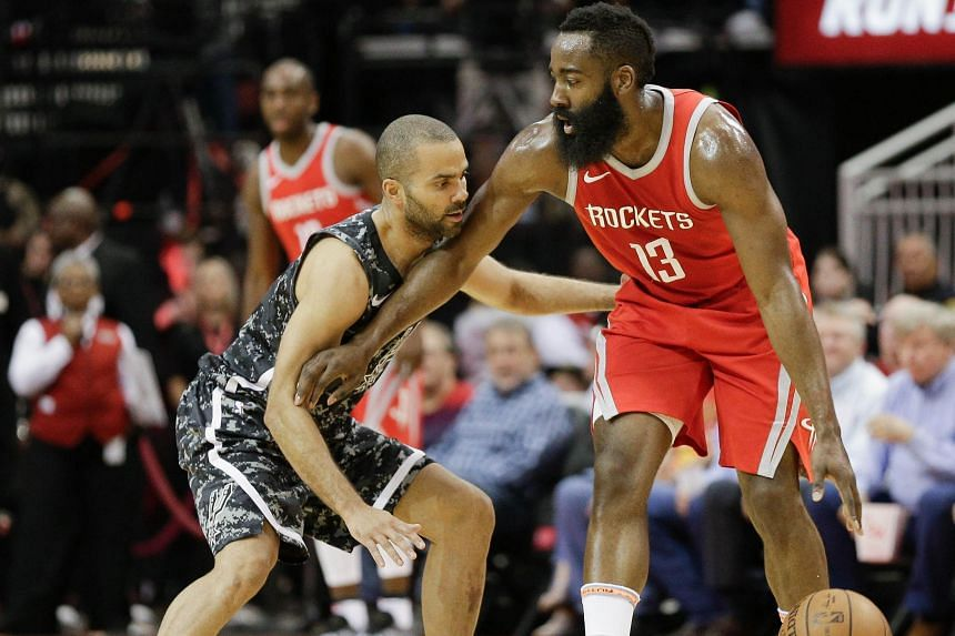 James Harden (right) of the Houston Rockets holds off Tony Parker of the San Antonio Spurs at Toyota Center on March 12, 2018 in Houston, Texas.