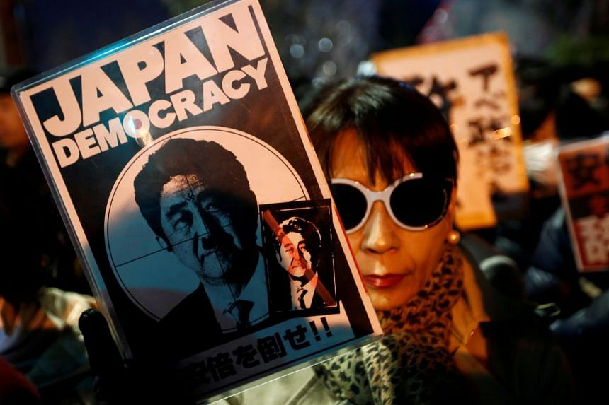 A protester holds a banner denouncing Abe at a rally in front of Abe's official residence in Tokyo.