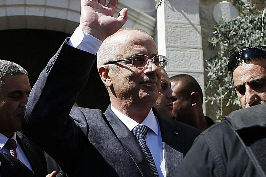 A damaged vehicle from the Palestinian Prime Minister's convoy being taken away yesterday after the attack near the Gaza Strip's northern town of Beit Hanoun. Palestinian Prime Minister Rami Hamdallah waving to the crowd upon his arrival in the West