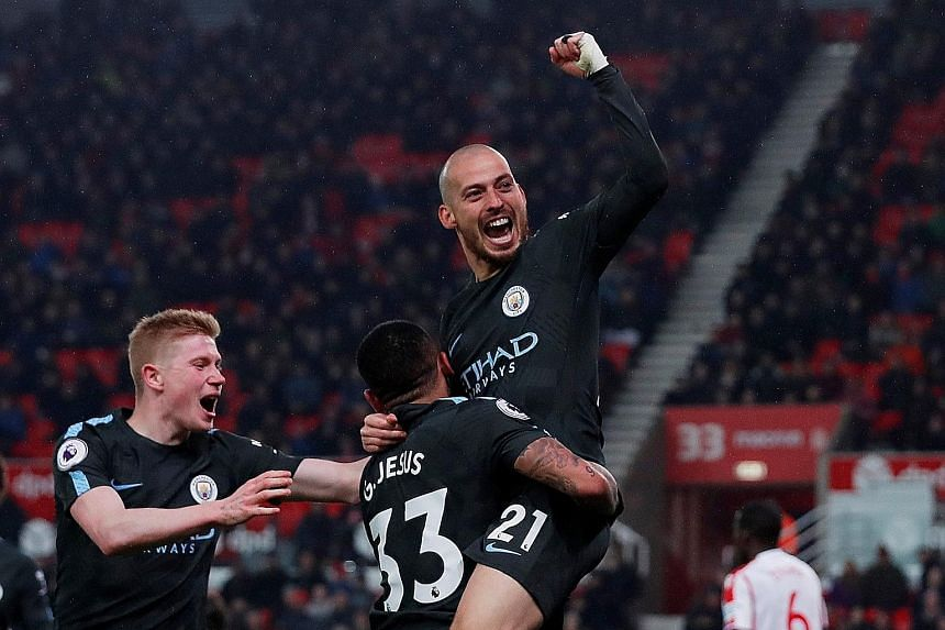 Manchester City's David Silva celebrating his second strike with the creator of the goal Gabriel Jesus, and Kevin de Bruyne. The Spaniard's double sealed three points on a cold, rainy night in Stoke as City moved closer to clinching the Premier Leagu