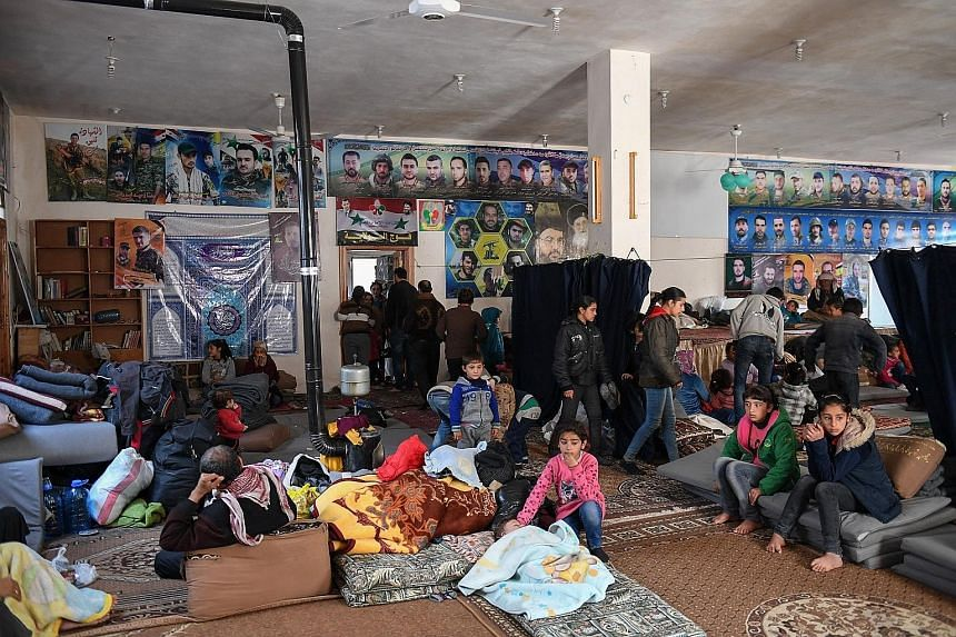 People fleeing the Turkish offensive on the Syrian Kurdish town of Afrin taking refuge in a shelter in Nubol, 26km north-west of Aleppo, yesterday. Analysts suggest Turkey will be content to lay siege to Afrin for some time while allowing civilians t