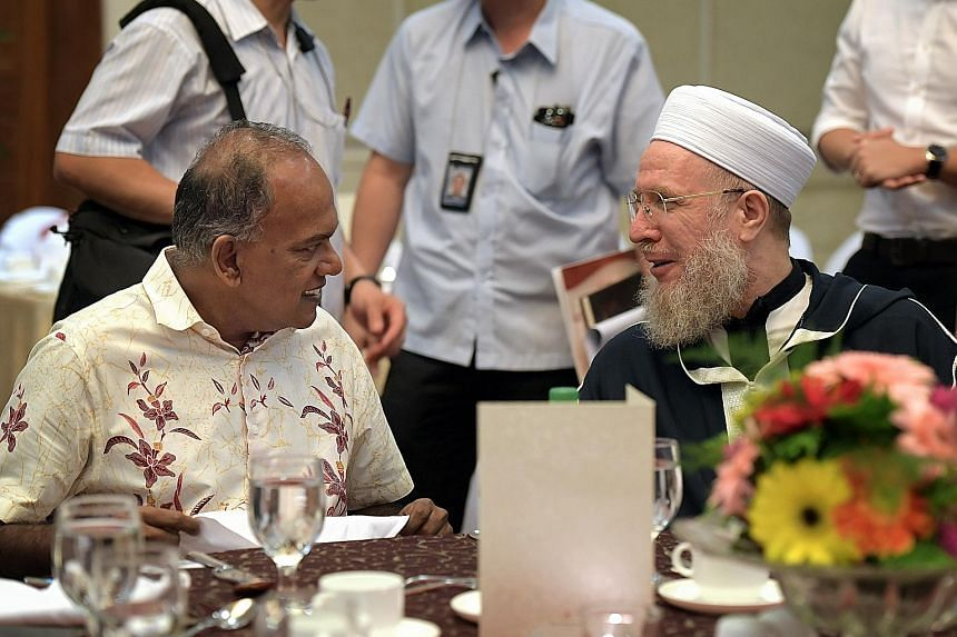Home Affairs Minister K. Shanmugam speaking with Syrian Islamic scholar Shaykh Sayyid Muhammad Al-Yaqoubi at the Religious Rehabilitation Group's 14th Annual Retreat yesterday.