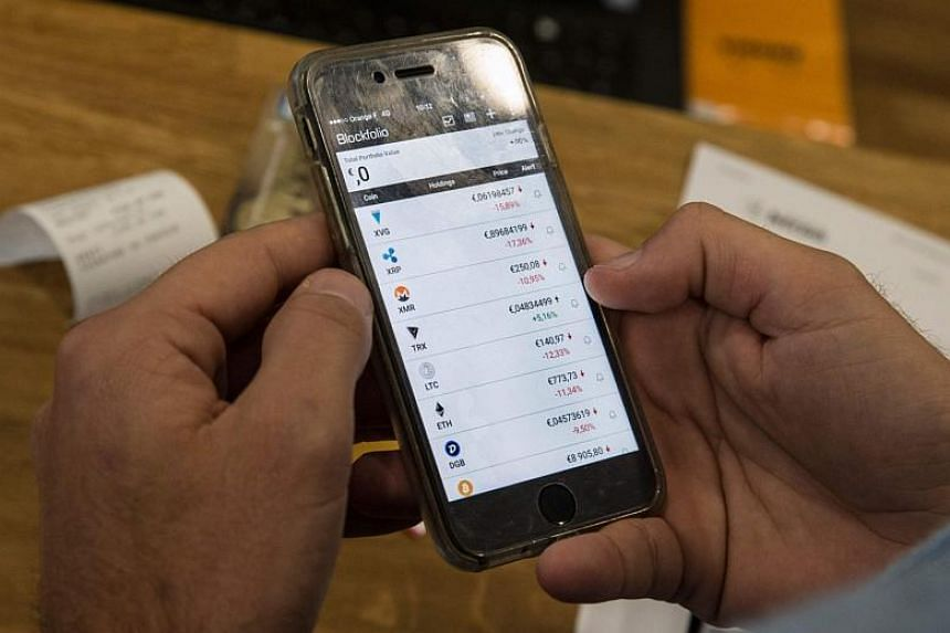 A persons looks at a cellphone displaying virtual currencies exchange rates. Google said it will ban advertisements for cryptocurrencies and related content starting in June.