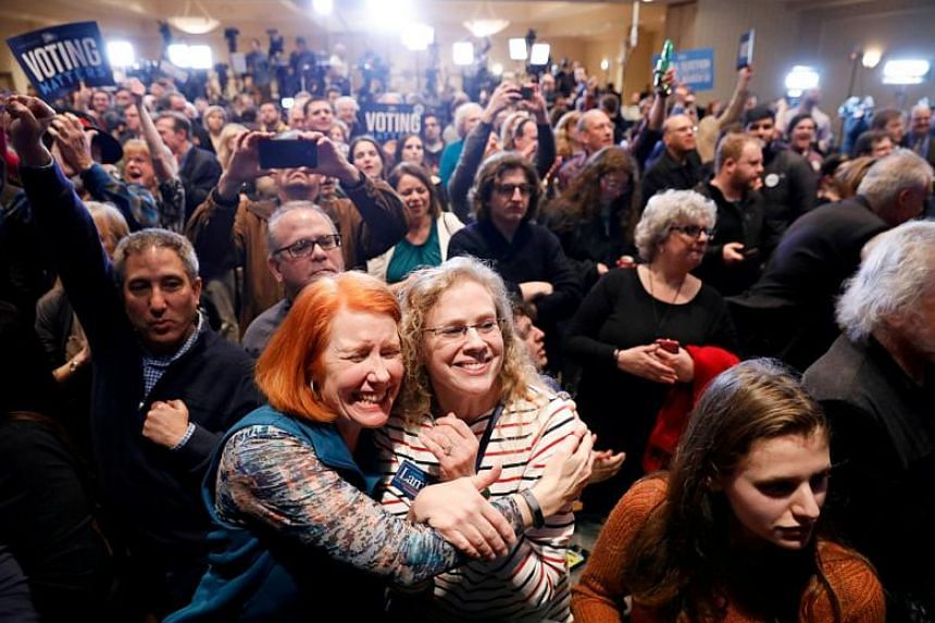 Supporters of US Democratic congressional candidate Conor Lamb react to the results coming in during Lamb's election night rally in Pennsylvania's 18th US Congressional district special election against Republican candidate Rick Saccone.