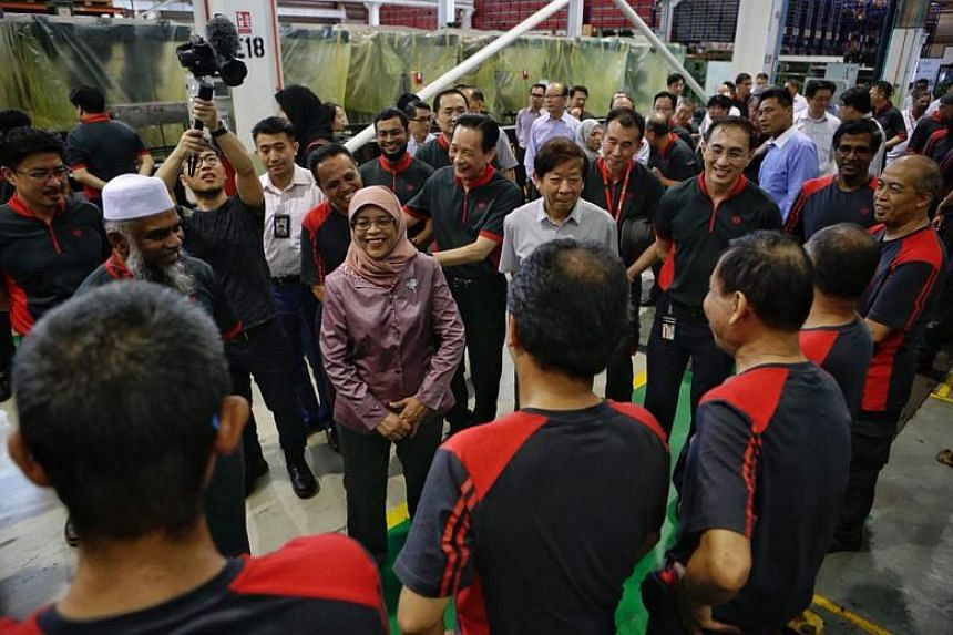 President Halimah Yacob meeting staff from the air-conditioning workshop during her visit to Bishan Depot on March 14, 2018.