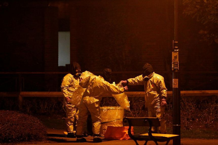 Members of the emergency services wear protective clothing as they work near the bench where former Russian intelligence officer Sergei Skripal and his daughter Yulia were found poisoned in Salisbury, Britain.