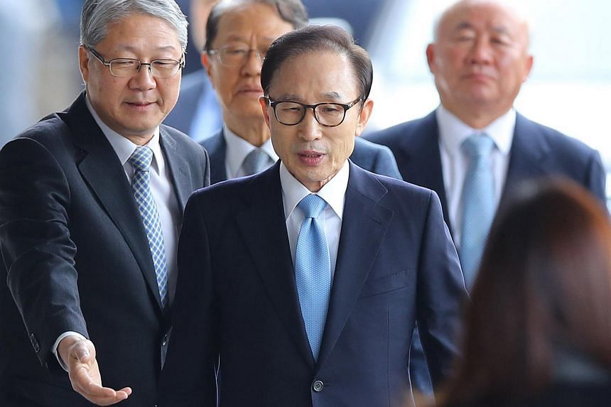 Former South Korean President Lee Myung Bak (centre) arrives at the Seoul Central District Prosecutors Office in Seoul for questioning on March 14, 2018.