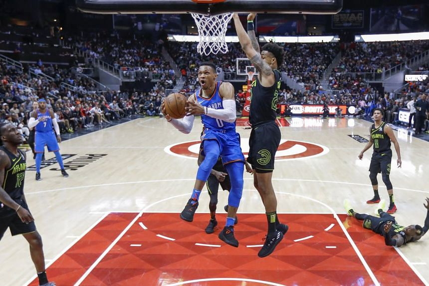 Oklahoma City Thunder guard Russell Westbrook (left) goes to the basket against Atlanta Hawks forward John Collins (right) during the second half of the game, on March 13, 2018.