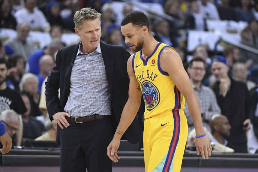 Golden State Warriors head coach Steve Kerr talks to guard Stephen Curry (right) after an injury against the San Antonio Spurs during the first quarter at Oracle Arena.