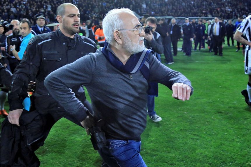 Owner of PAOK Salonika, Ivan Savvides (centre), enters the pitch with what appears to be a gun in a holster after the referee annulled a goal of PAOK during their soccer match against AEK Athens in Toumba Stadium in Thessaloniki, Greece, on March 11,