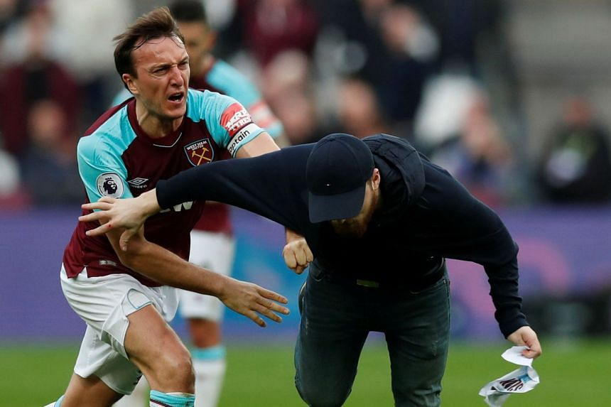 West Ham United's Mark Noble clashes with a fan who has invaded the pitch.