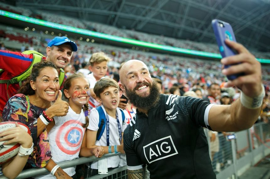 A family takes a selfie with All Black Sevens legend DJ Forbes.