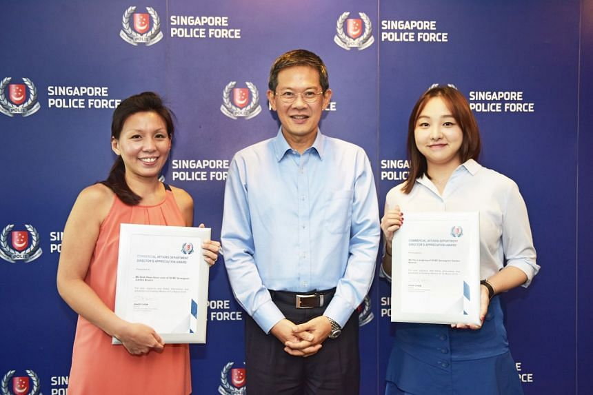 Ms June Seah (left) and Ms Yao Liang Bing (right) receiving the awards presented by Mr David Chew (centre) for successfully preventing an Internet love scam.