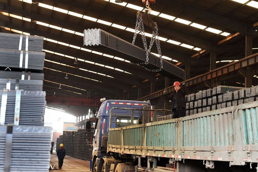 Workers load steel in a workshop in Zouping, in China's eastern Shandong province on March 10, 2018.