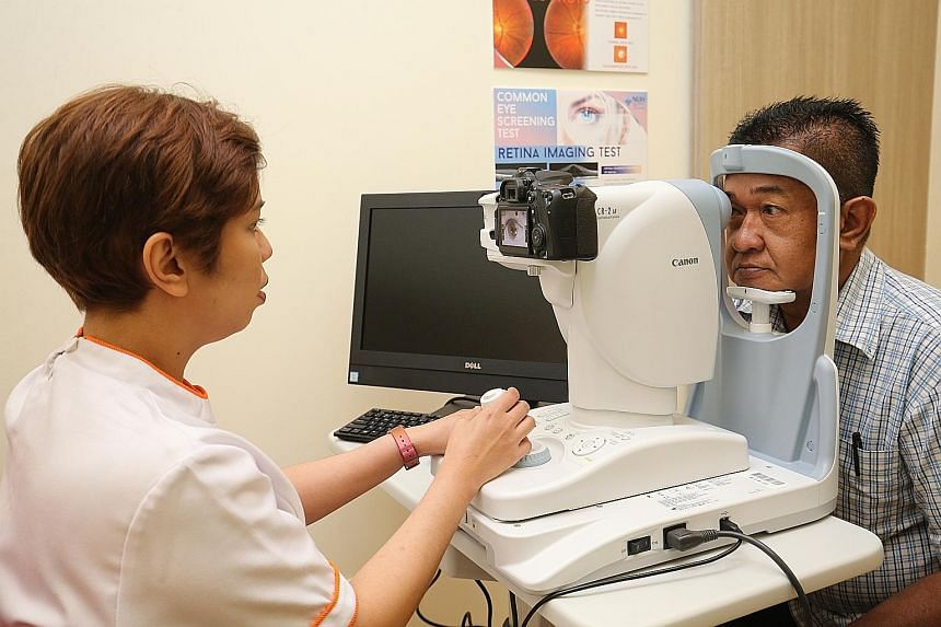 NUH senior enrolled nurse Nurhidah Afendi performing a diabetic retinal photography service for Mr Abdul Razak Abdul Rahman at Keat Hong Family Medicine Clinic. The 58-year-old diabetes patient said he finds the clinic more convenient than polyclinic