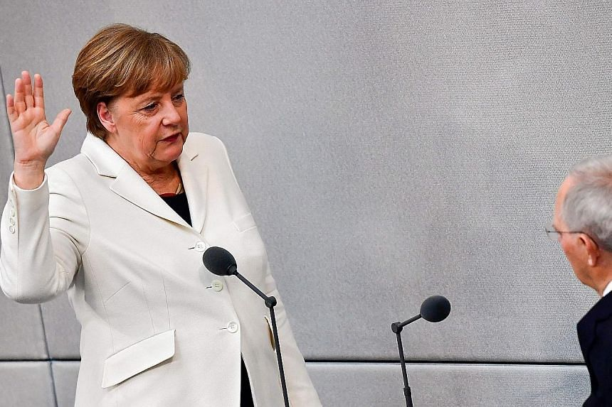 German Chancellor Angela Merkel being sworn in for her fourth term in office by the president of the Lower House of Parliament Wolfgang Schaeuble yesterday.