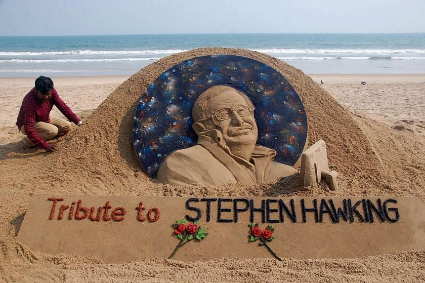 Sand artist Sudarsan Patnaik giving final touches to a sculpture at India's Puri Beach yesterday in honour of British cosmologist Stephen Hawking, who died at the age of 76 yesterday.