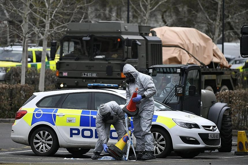 Military personnel in protective clothing removing vehicles from a carpark in Salisbury on Sunday. Former Russian spy Sergei Skripal and his daughter Yulia had been attacked with a nerve agent on March 4 in the area.