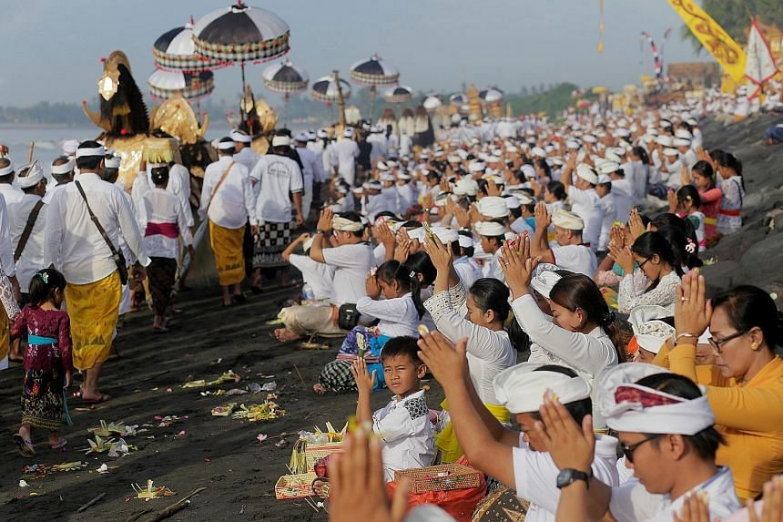 Hindus praying on a Bali beach yesterday during a purification ceremony ahead of the holy day of Nyepi. The Indonesian tourist island falls silent during the annual observance of Nyepi, the religious holiday which marks the Balinese new year. Islande